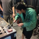 Alisha pouring hot metal alloy into her mold